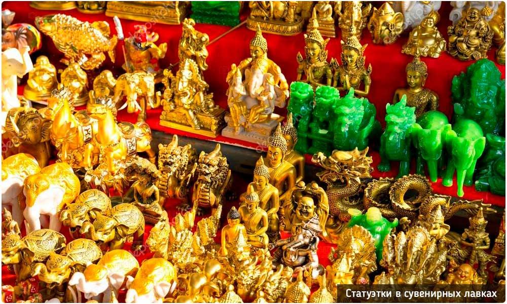 Статуэтки слонов и Будды на тайских прилавках